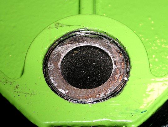 Фотографии дополнительных приспособлений к стойке для дрели. (а) - толстостенная труба, установленная с натягом в нижнюю часть штанги (вид со стороны нижней части станины), (б) - ручка, установленная на фланец взамен штатного рычага (вывернут), (в) - новая пружина, установленная взамен штатной (она для сравнения показана справа).