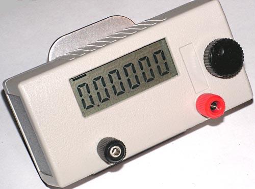 Общий вид вольтметра в сборе. (а) - вид с лицевой стороны, (б) - вид с обратной стороны на подставке для телефона.